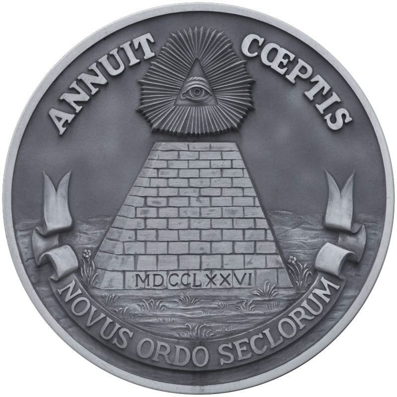 The reverse of the Great Seal of the U.S. includes the eye of providence looking over an unfinished pyramid representing the 13 original states. The images and bottom motto – Latin for