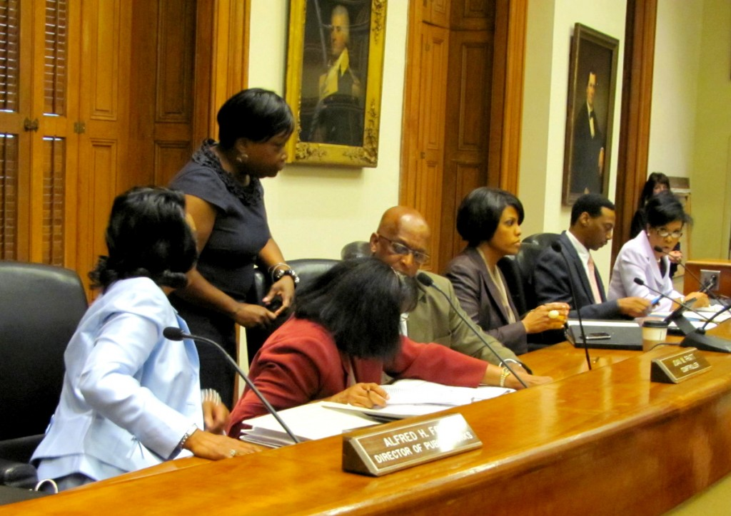 Pratt and Young confer with their aides, while Rawlings-Blake cradles a cup of coffee before the vote on the IBM contract. (Photo by Mark Reutter)