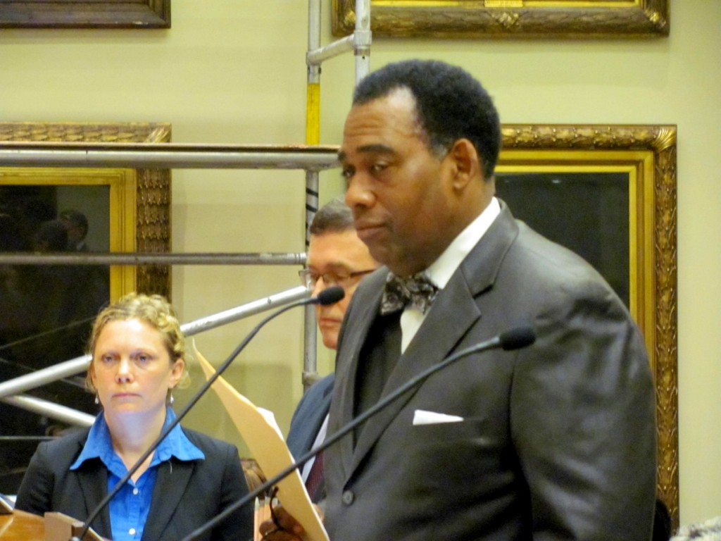 Robert Minor speaks before the board, with a member of the law department listening. (Photo by Mark Reutter)
