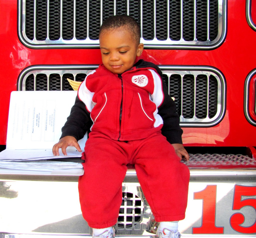 Sixteen-month-old Anton Manning looks at signatures by East Baltimore residents petitioning to keep Fire Company 15 open. City Hall closed the company without the benefit of any financial audit. (Photo by Mark Reutter)