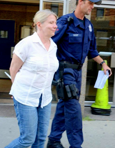 Activist Sharon Black being escorted to Central Booking today after being arrested at City Hall for trespassing. (Photo by Wiliam Hughes)
