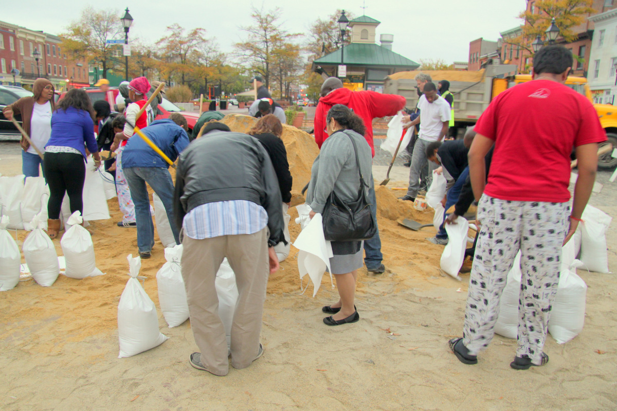 The city sandbag distribution station at the end of Broadway in Fells Point was busy throughout the day. (Photo by Fern Shen)