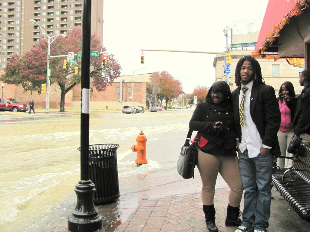 Briana Hamlett and Devon Horton were waiting for a bus to get to school this morning, but were stranded at Charles and North amid a tide of rushing water. (Photo by Mark Reutter)
