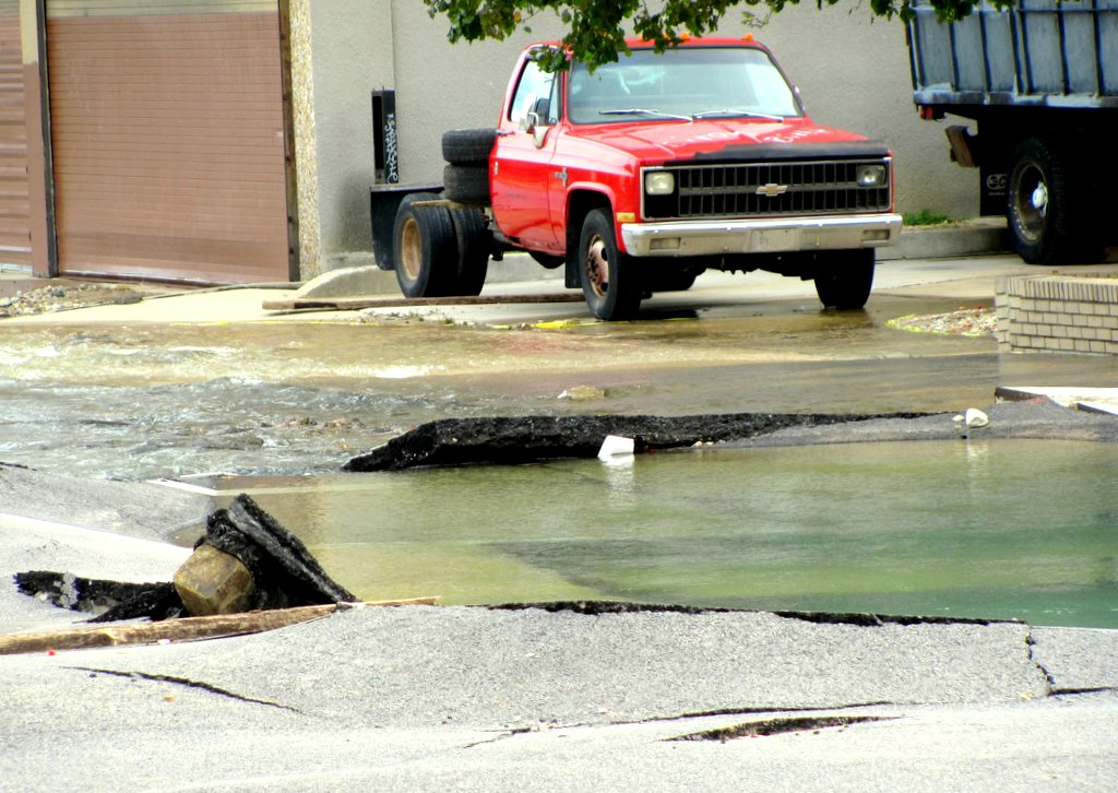 Thick slabs of asphalt buckled under the force of the water main break. Water seeps through a dozen cracks at 20th Street. (Photo by Mark Reutter)