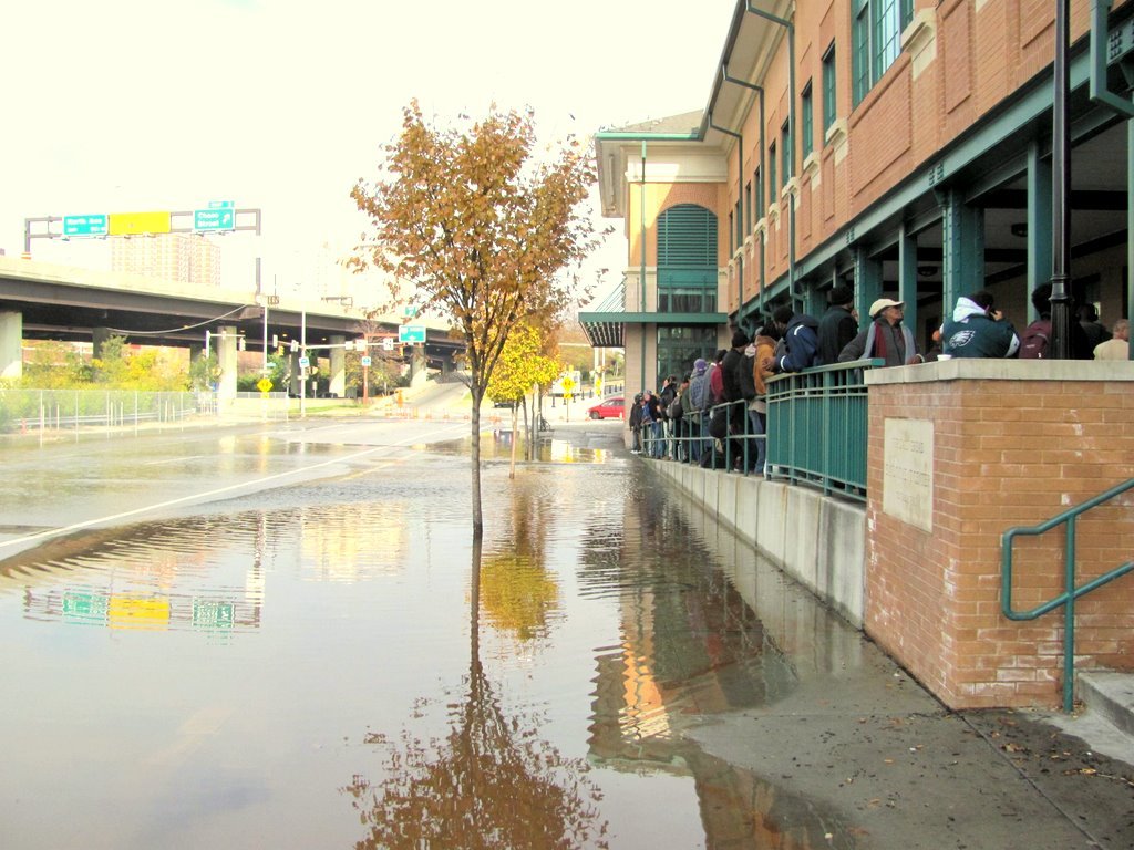 A crowd waiting for food this morning at Our Daily Bread soup kitchen on Fallsway look at water lapping up beside the building. (Photo by Mark Reutter)