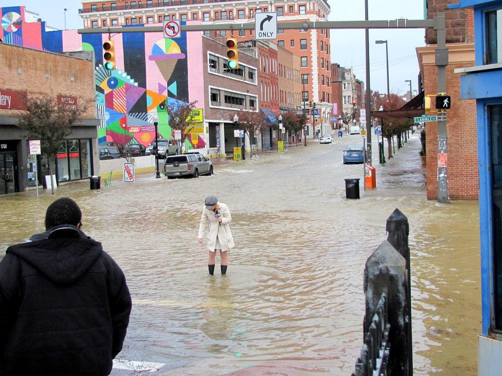 A Fox 45 reporter reenacts the media's knee-deep-in-the-water Sandy coverage at Charles and Lanvale streets. (Photo by Mark Reutter)