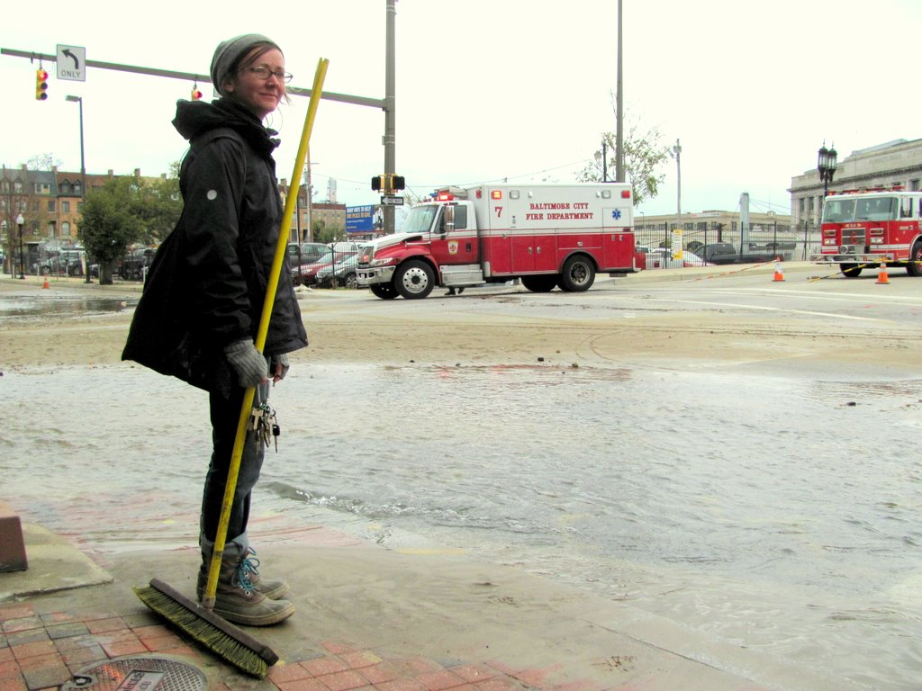 Marian Glebes takes a break from sweeping away the sand that accumulated at the intersection of Charles and Lanvale streets today. (Photo by Mark Reutter)