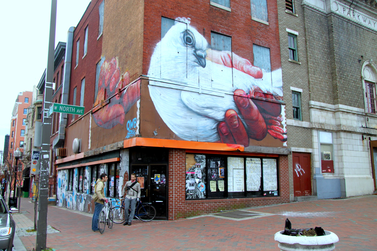Keeping with the fowl theme, street artist Gaia put a carrier pigeon on the exterior of the New York Fried building, part of Station North's Open Walls project. The Parkway Theatre is at right. (Photo by Fern Shen)