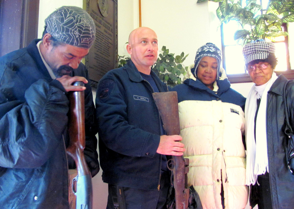 Wayne and Angenetta Johnson (left) and Geneva McBride traded in old shotguns. Officer Kevin Gesla stands between the Johnsons. (Photo by Mark Reutter)