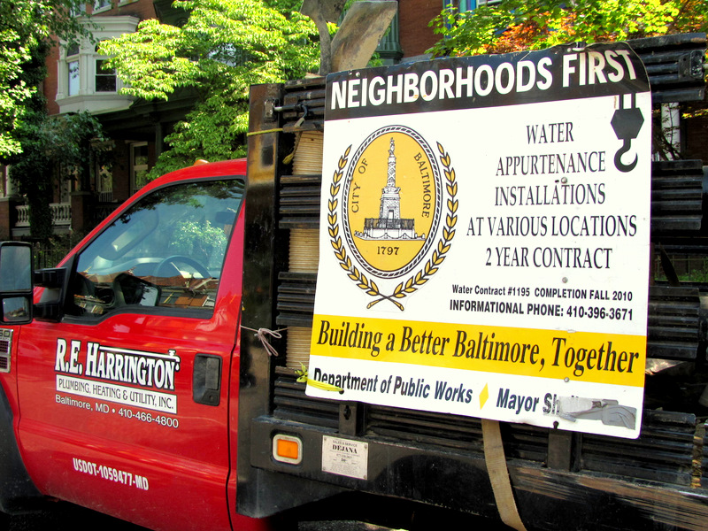 A Harrington company truck displays a water contract that was awarded in the era of former Mayor Sheila Dixon. The crew was repairing a fire hydrant at Calvert and 27th streets last July. (Photo by Mark Reutter)