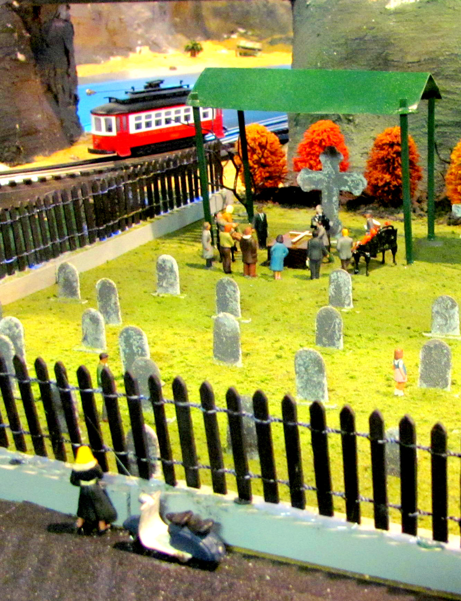 This burial scene has a wry twist courtesy of the blond figure looking in over the fence. (Photo by Mark Reutter)