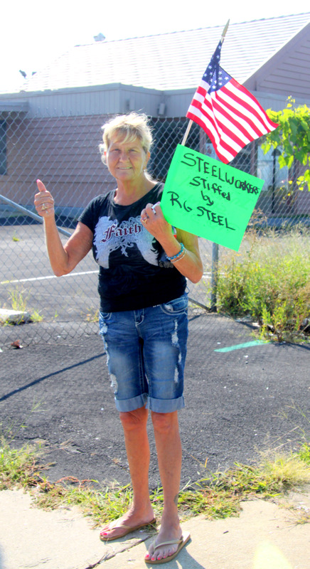 Alice Lambert holds up a sign on Dundalk Ave. last summer expressing solidarity with steelworkers who lost their jobs. (Photo by Fern Shen)