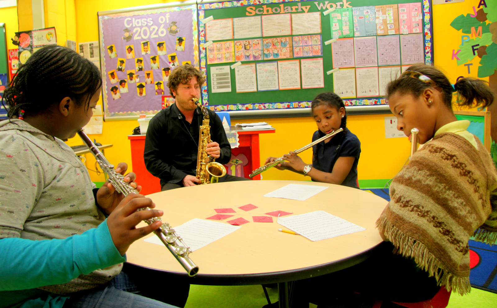Russell Kirk works with the OrchKids flutists, (l to r) Dashney White, Kaneese Mack and Dia Simmons. (Photo by Fern Shen)