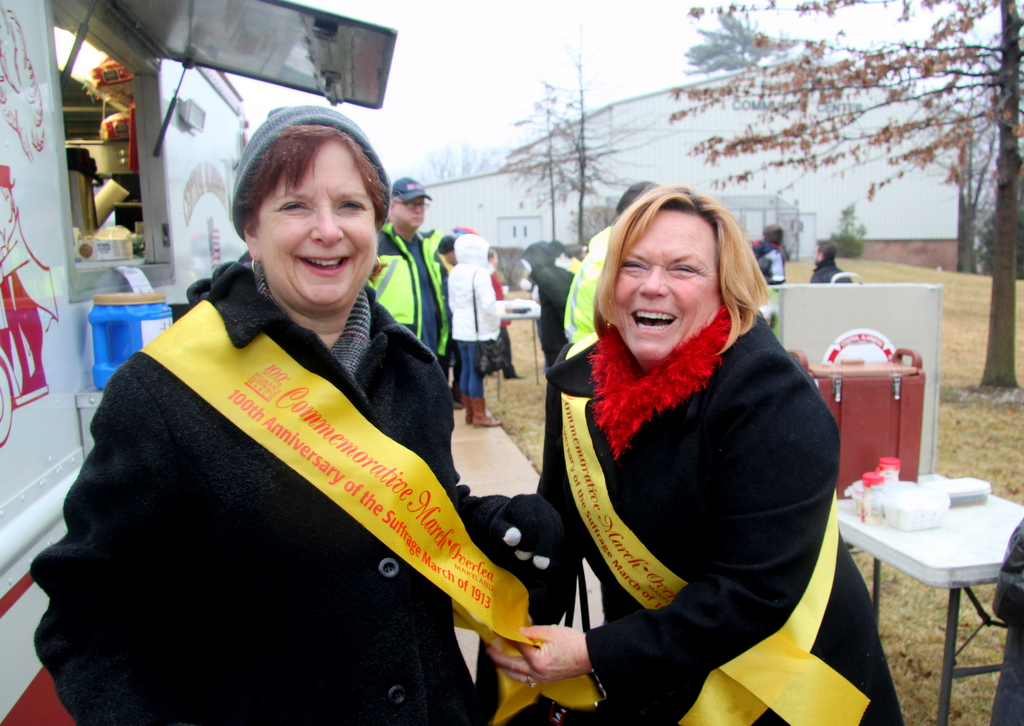 Baltimore County Councilwoman Cathy Bevins helps State Senator Katherine A. Klausmeier with her sash. (Photo by Fern Shen)
