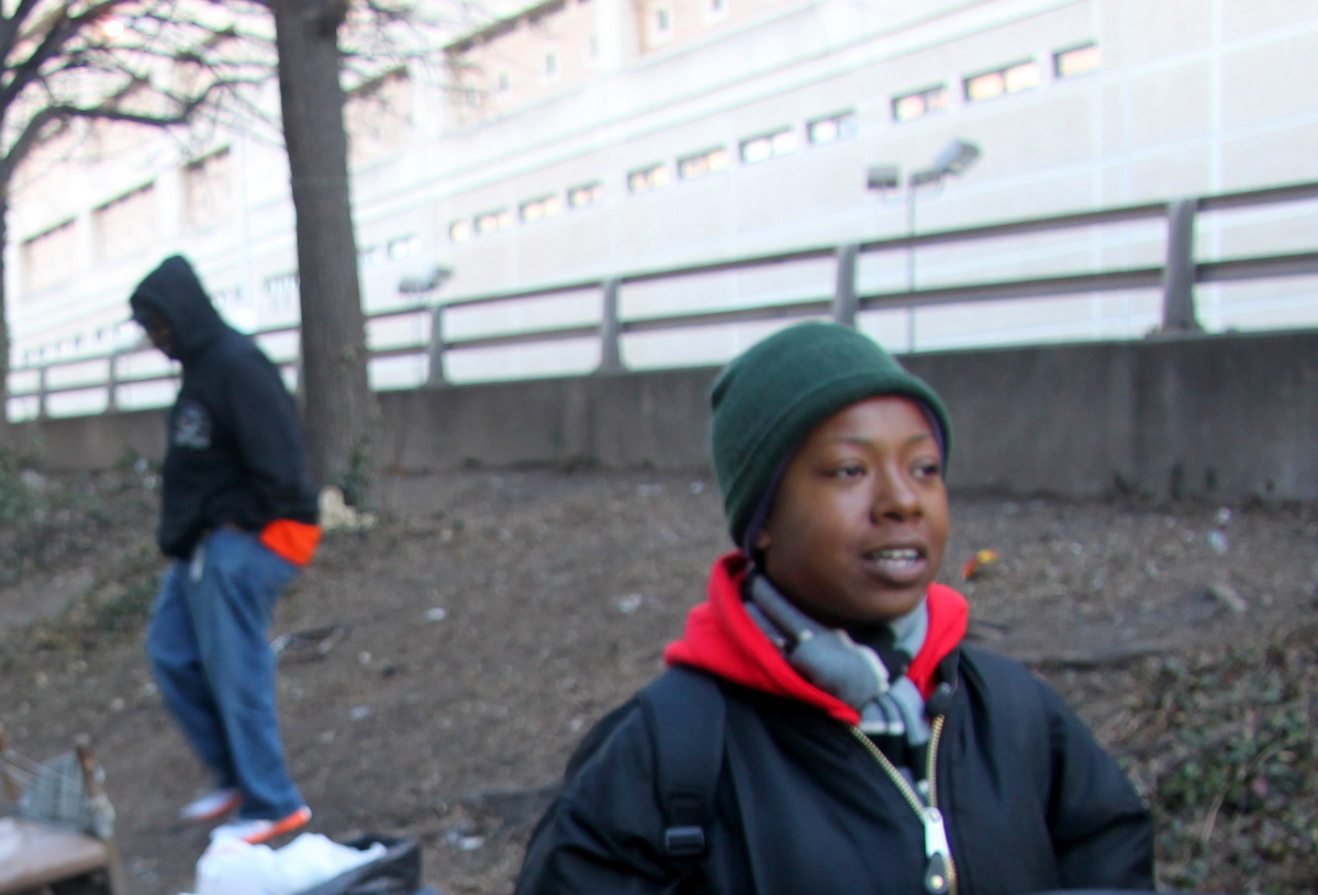 Tracy Jones, a former resident of Camp 83, watching city workers clearing away the encampment. (Photo by Fern Shen)