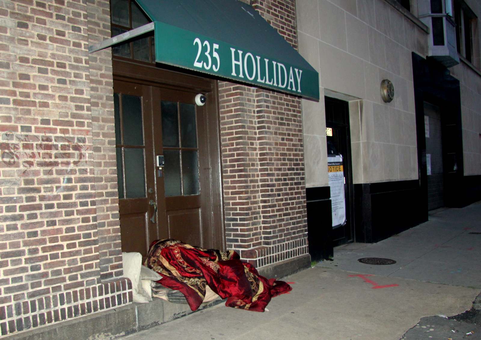 Someone sleeping in a doorway, a block from City Hall, after the council meeting adjourned. (Photo by Fern Shen)
