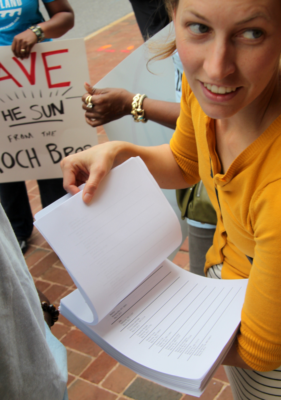 Molly Porter, of Good Jobs, Better Baltimore, holding petition against the Kochs signed by 6,5000 people. (Photo by Fern Shen)