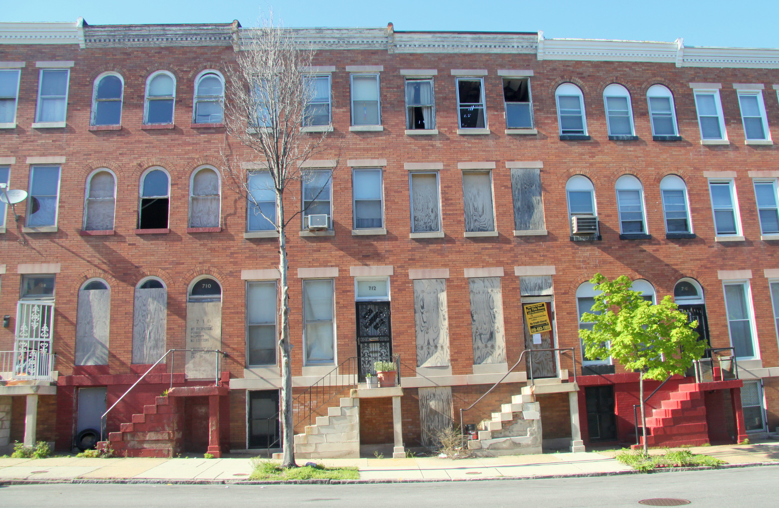 Vacant and dilapidated 714 E. 21st St. has occupied homes on either side. (Photo by Fern Shen)