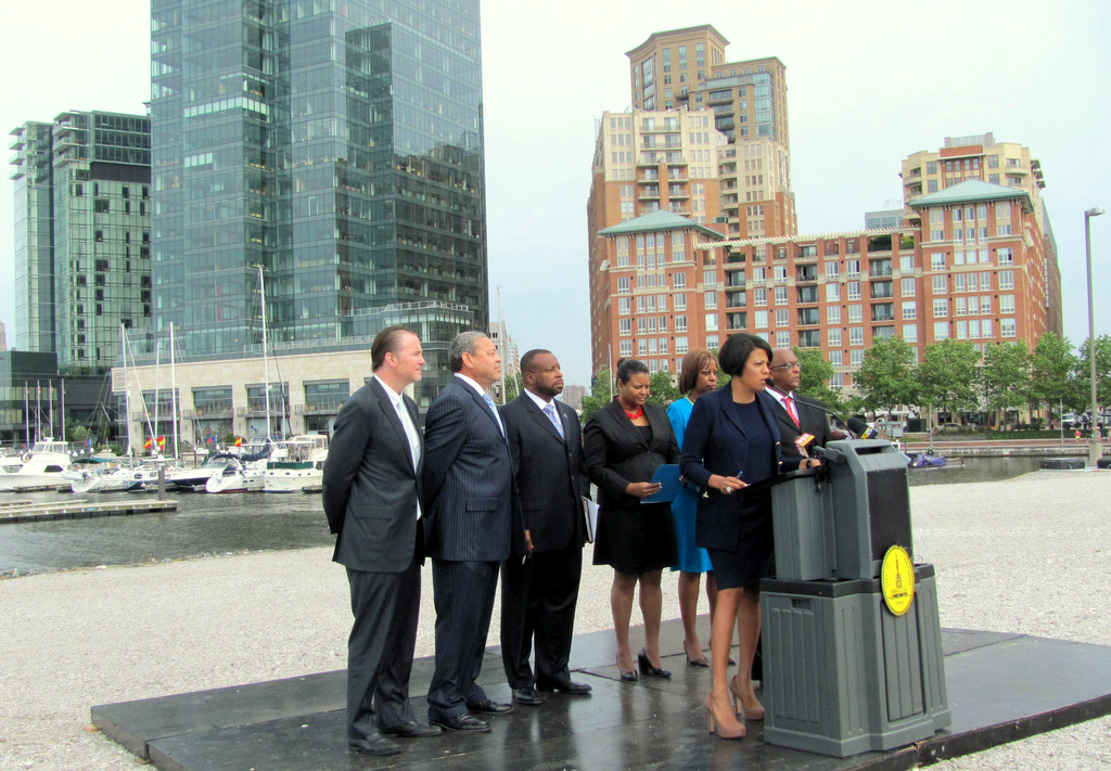 Michael Beatty (left) listens to Mayor Rawlings-Blake extol his project at press conference yesterday. The conference was held on the cleared site, with the Harbor East skylight as a camera-friendly backdrop. (Photo by Mark Reutter)  backdropped by Harbor East.