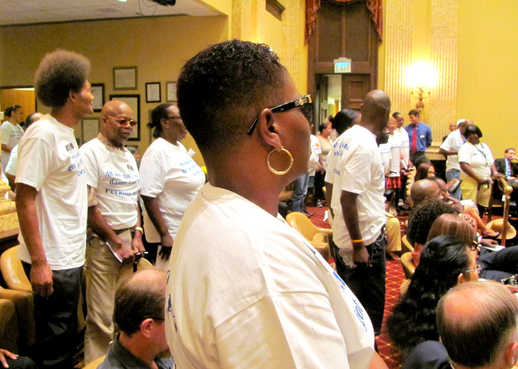 Donnetter Herndon (foreground) and other Perkins Homes residents stan dup at hearing. (Photo by Mark Reutter)