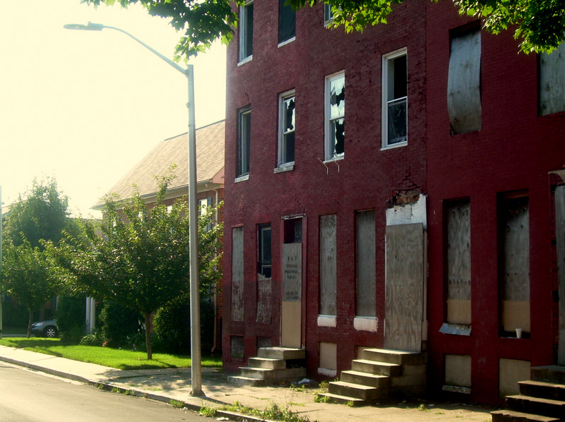 The contrast between Heritage Crossing (left) and the wrecked rowhouses next door on Brune Street illustrates the absence of economic stimulus on the Westside. (Photo by Gerald Neily)