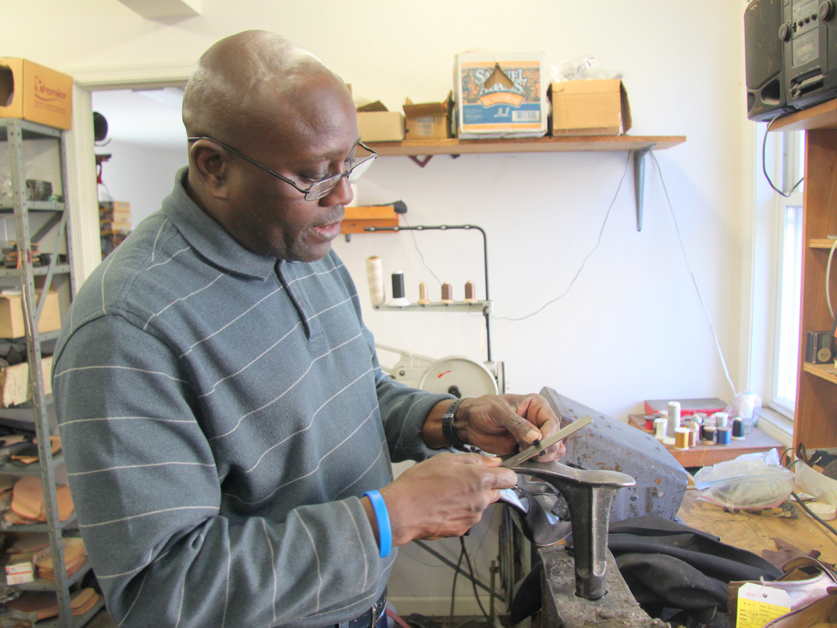 Curtis Sample, repairing the elastic on a high-heeled shoe. (Photo by Fern Shen)