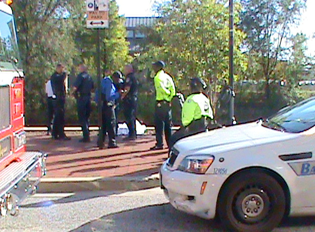 Police stand beside body in the white sheet. Below: a sneakered foot protrudes from the sheet. (Both by Kim Krueheart)
