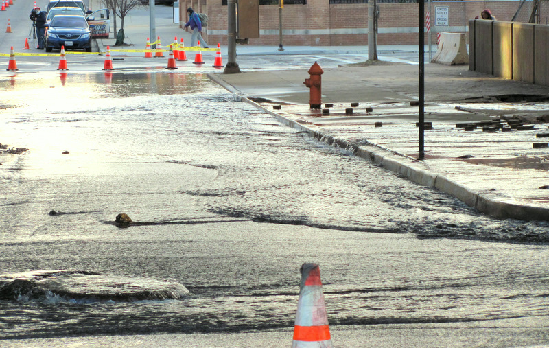Water spurts out of the cracked pavement and manholes at 8:30 this morning. (Photo by Mark Reutter)