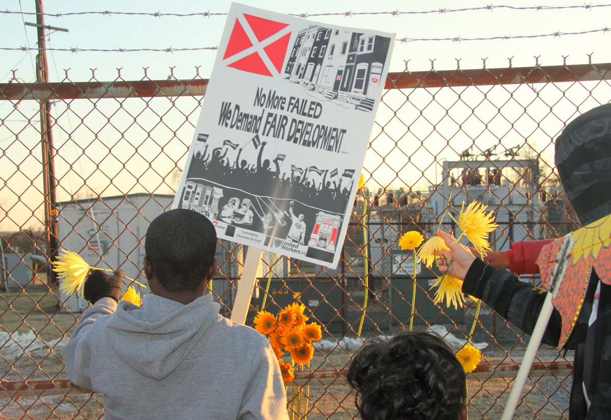 Students left flowers at the fence of a former chemical plant in South Baltimore where a trash incinerator is proposed.