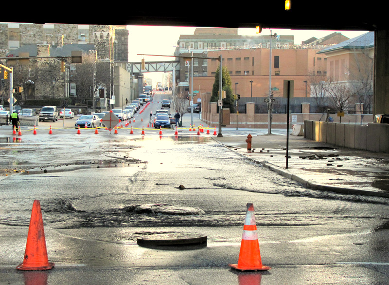Water gushes from a broken 20-inch water main at Madison Street under the Jones Falls Expressway this morning.
