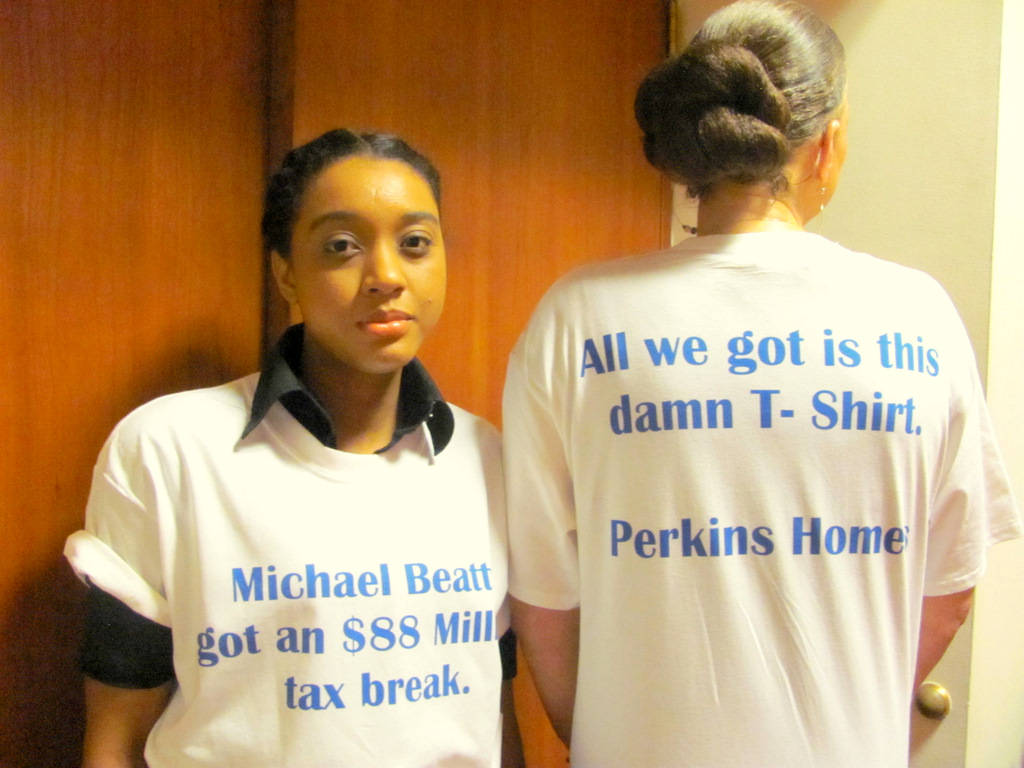 Coleen Duncan and Monica Brown model t-shirts worn by Perkins Home residents upset by financial benefits secured by developer Michael Beatty. (Photo by Mark Reutter)