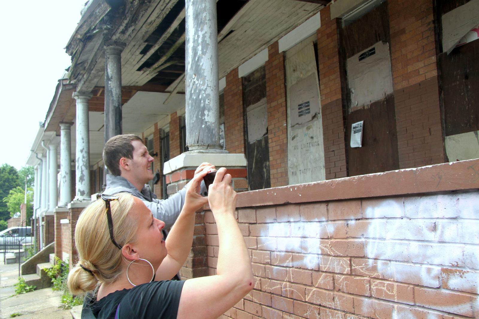 Carol Ott at work with street artist Nether in Northwest Baltimore. (Photo by Fern Shen)
