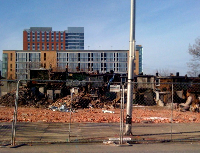 Rubble from the demolition of several blocks of East Baltimore housing in 2014, with new graduate student dorm in the background. (Melody Simmons)