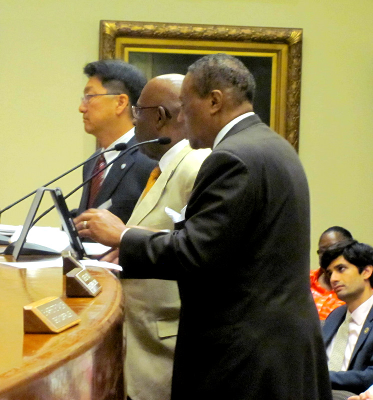 Arnold Jolivet argues a point before the Board of Estimates while Thomas Corey, chief of the minority business office, and Rudy Chow, then DPW water chief, listen.