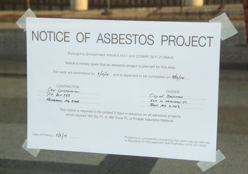 A notice taped on the windows of the Arena warns that an asbestos project is underway there. (Photo by Fern Shen)