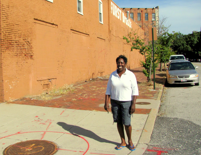 Betty Bland-Thomas next to one of the vacant industrial properties slated to be torn down on Leadenhall Street for the Stadium Square complex. (Photo by Mark Reutter)