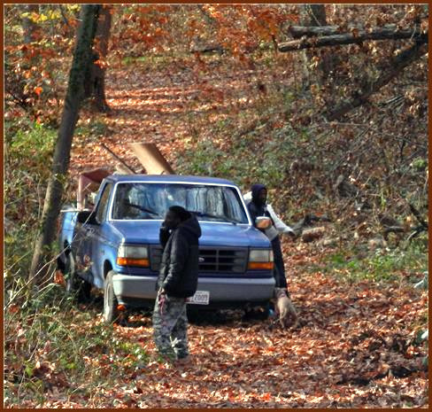 Several people milled around the loaded pickup truck that was found stuck in Herring Run Park. (Photo by Patty Dowd)