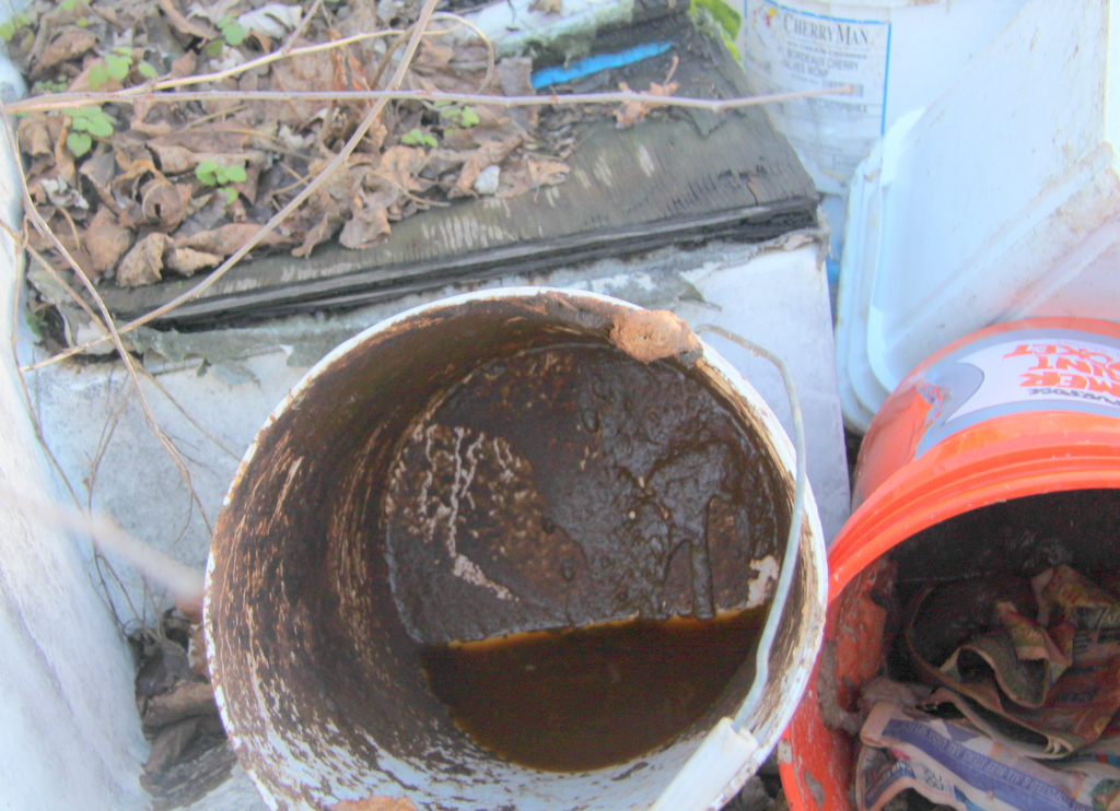 A fecal odor wafted from the buckets in the boat. (Photo by Fern Shen)