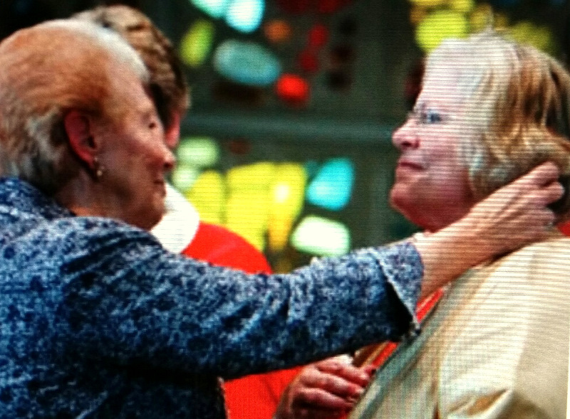A family member places the pectoral cross on Heather Cook at her ordination. (Maryland Episcopalian, Fall 2014)
