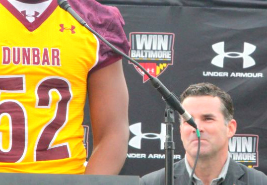 Under Armour CEO Scott Plank sits a 2012 ceremony rich with UA branding honoring the company's donation of a artificial-turf football field for Dunbar High School.