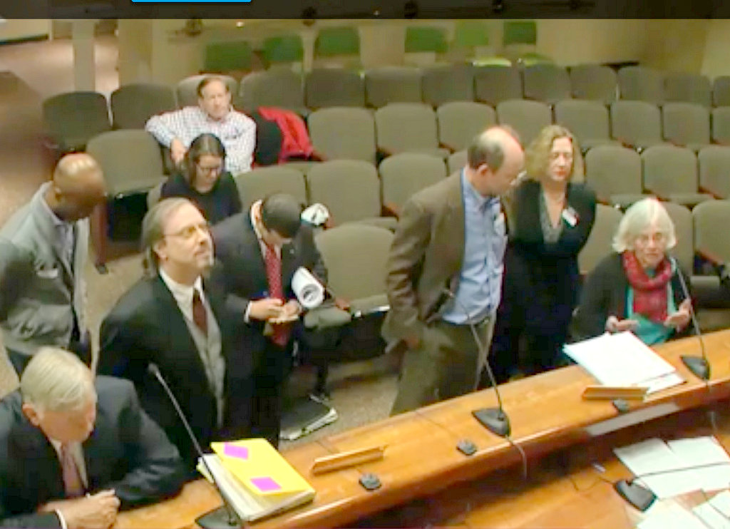 Charles Village Civic Association president Sandy Sparks, at right in red scarf, testifies against the license transfer requested for 2022 N. Charles Street. (YouTube)
