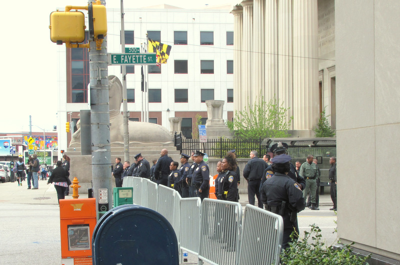 Officers stand behind a barrier at Fayette and Gay streets protecting police headquarters a block to the east. (Photo by Mark Reutter)