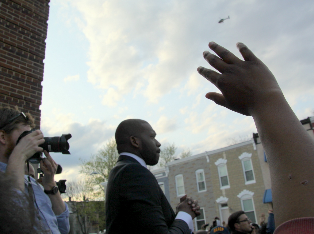 Rev. Jamal Bryant asks the crowd for quiet, as Freddie Gray's family members mourn. (Photo by Fern Shen)