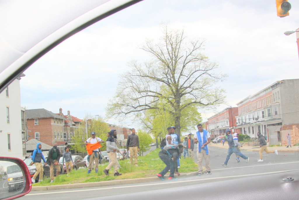 This group was lobbing rocks over the moving traffic at police on the other side. (Photo by Fern Shen)