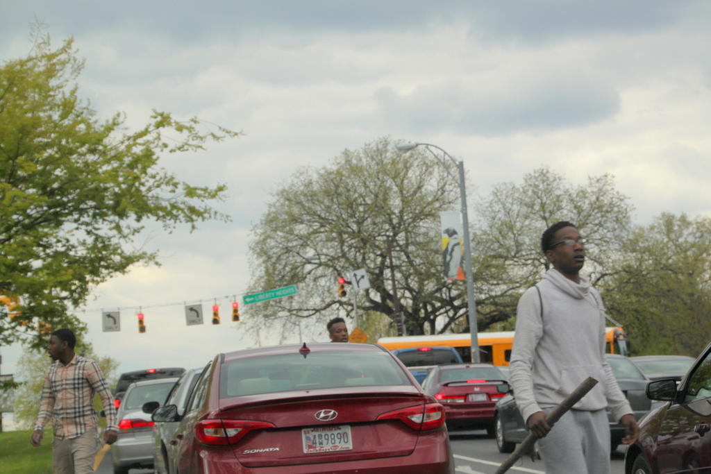 Young people, with sticks and rocks, walk through traffic on Druid Park Lake Drive. (Photo by FernShen)