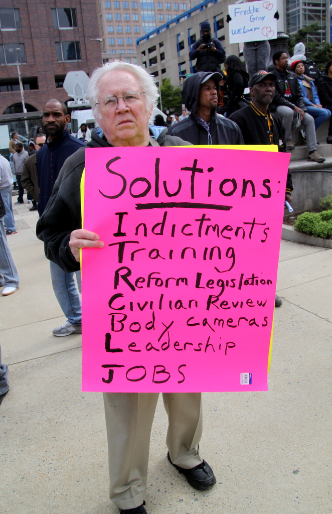 One of the signs held up outside City Hall focused on solutions. (Photo by Fern Shen)