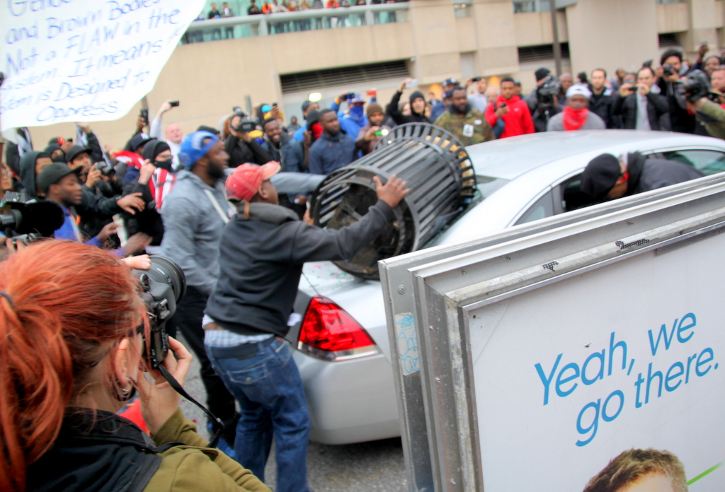 Demonstrators bash a car parked on Howard Street  with a metal trash can. (Photo by Fern Shen)