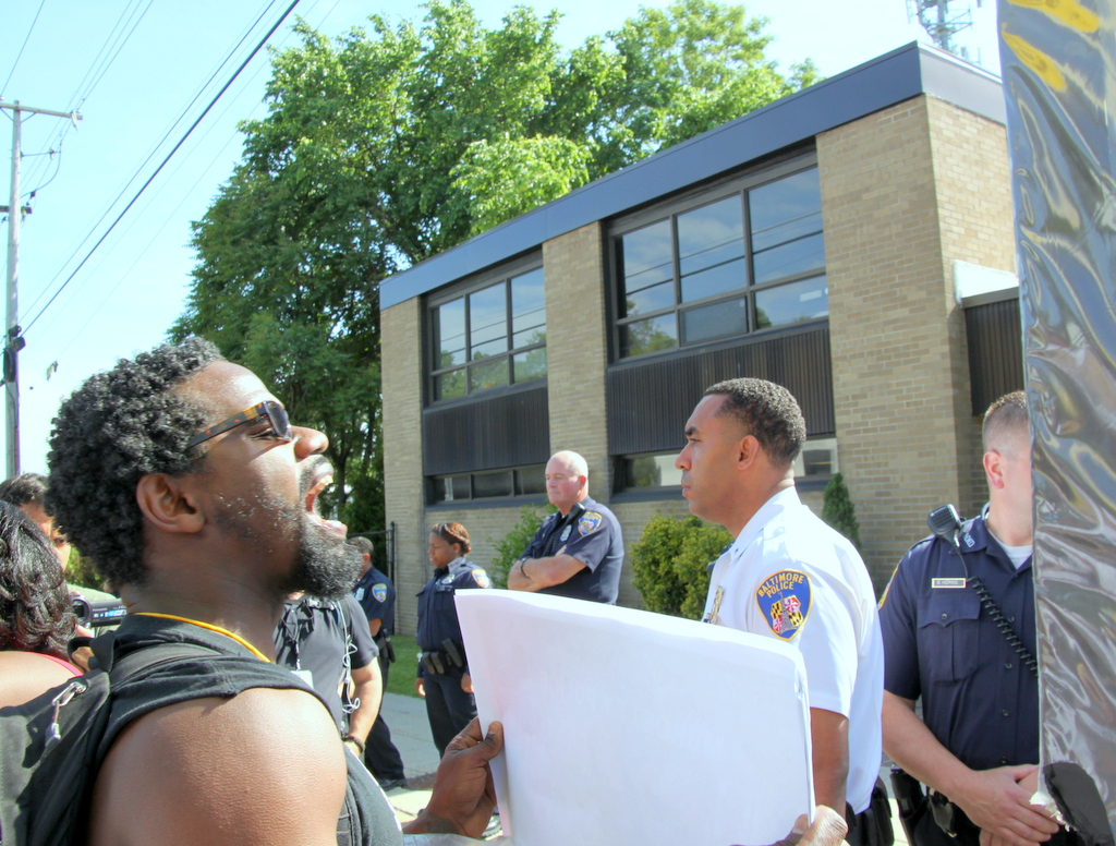 Police stood silently in a line facing protesters in front of FOP headquarters. (Photo by Fern Shen)