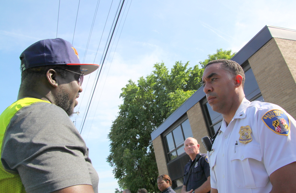 Lawrence Brown addresses Lt. Hans Nicolas, outside FOP headquarters in Baltimore.