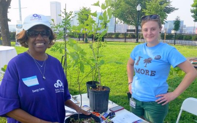 Stephanie Helms of the Office of Sustainability's Tree Baltimore program, gives Samantra Brightful a sapling.  (Photo by Ben Halvorsen)